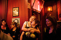 Caitlin Johnson hugs her friend, Carrie Davis, as they watch live music at The Riptide, in the Outer Sunset, San Francisco, on Saturday, Oct. 23, 2010. Originally known as the Oar House and has seen the likes of Herb Caen and fishermen, The Riptide is a knotty-pine dive bar that features surf flicks on Wednesdays and bingo on Saturday evenings.