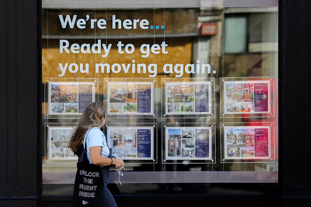 © Licensed to London News Pictures. 02/09/2020. London, UK. A woman views a display of properties for sale in an estate agent's window. According to new figures released by Nationwide, UK houses prices were at an all-time high in August 2020 after their biggest monthly rise since 2004, as buyers took advantage of a stamp-duty holiday. The average sale price of a home jumped £3,188 to £224,123 in August. Photo credit: Dinendra Haria/LNP
