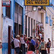 Tourists wait outside the famous La Bodeguita del Medio brain La Habana Vieja. The bar was made famous by Ernest Hemingway.<br />