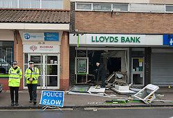 © Licensed to London News Pictures.  03/04/2015. Bristol, UK.  Police forensics examine extensive damage to a branch of Lloyds Bank on Shirehampton High Street which was raided last night at around 2am.  A teenager has been arrested in connection with the incident.  Photo credit : Simon Chapman/LNP