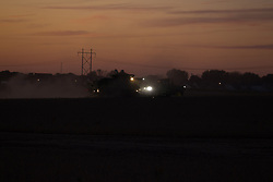 18 October 2017:   At the cities edge, a farmer picks soybeans at dusk with a sunset over the city in the background