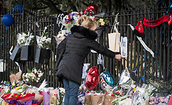 © Licensed to London News Pictures. 28/01/2018. London, UK. A woman looks at tributes left at the scene where three teenage pedestrians were killed near a bus stop in Hayes, West London when a black Audi collided with them. Named locally as Harry Rice, Josh Kennedy and George Wilkinson, the three teenagers were hit on Friday night  close to the M4 Junction 4. A 28-year-old man has been arrested and a police are currently looking for a  second man believed to have been in the Audi.. Photo credit: Ben Cawthra/LNP