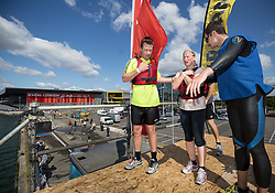 © Licensed to London News Pictures. 25/07/2015. London, UK. Runners taking part in the 10k London River Rat Race at the Docklands in east London. The obstacle course consisted of several challenges including a 20ft freefall jump, monkey bars and water trampolines.   Photo credit : James Gourley/LNP