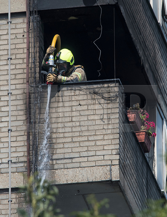 © Licensed to London News Pictures. 23/08/2019. London, UK. A fire fighter hoses down the exterior of the building at the scene where a fire has started at a flat in a tower block at Darfield Way in west London, just yards from Grenfell Tower. Photo credit: Ben Cawthra/LNP