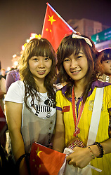 Chinese girls wait to see the closing ceremony in a commericial zone during the Beijing 2008 Olympic Games  August 24, 2008. (Photo By Ami Vitale)