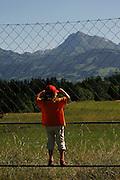 Un garçon / une fille grimpe sur un grille pour admirer le paysage gruèrien avec le Moléson, Sorens, place de foot, juin 2009.  Ein Bub klettert einen Zaun hoch um die Greyerzer Landschaft zu betrachten. Im Hintergrund der Moléson, Sorens, Fussballplatz, Juni 2009.