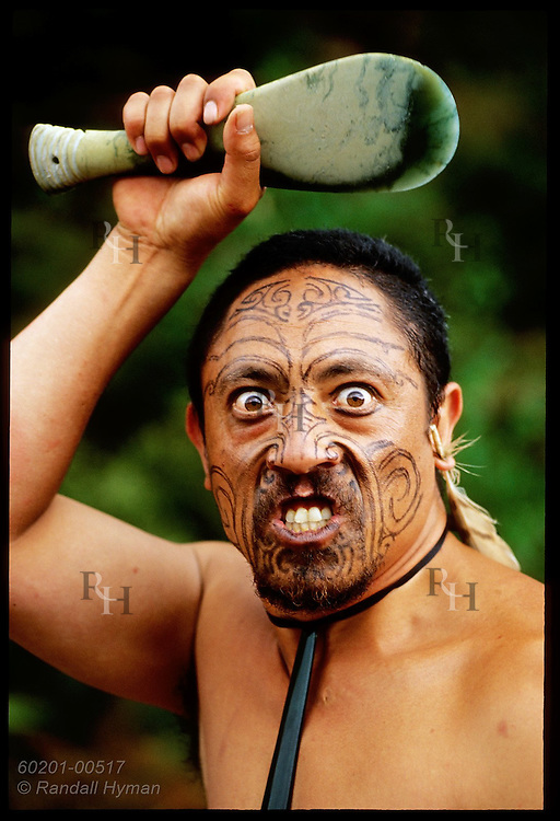 Traditional Maori performer grimaces as he threatens with paddle at Waimangu Volcanic Valley; Rotorua, New Zealand.