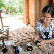 BAGAN, Myanmar - A women etches designs into black lacquerare near the entrance to Naga Yon Hpaya Temple in Bagan. Naga Yon Hpaya Temple, one of thousands of stupas on the plain of Bagan, features ornate stucco work and painting inside and is in the process of being renovated. It has dark internal corridors with strategically placed windows that capture the sun to shine light on the main Buddha statue as well as various statues in alcoves lining the corridors.