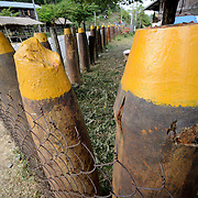 Unexploded munitions left over from the Vietnam War are used as fence posts in a village in the Plain of Jars, Laos, known as Bomb Village.