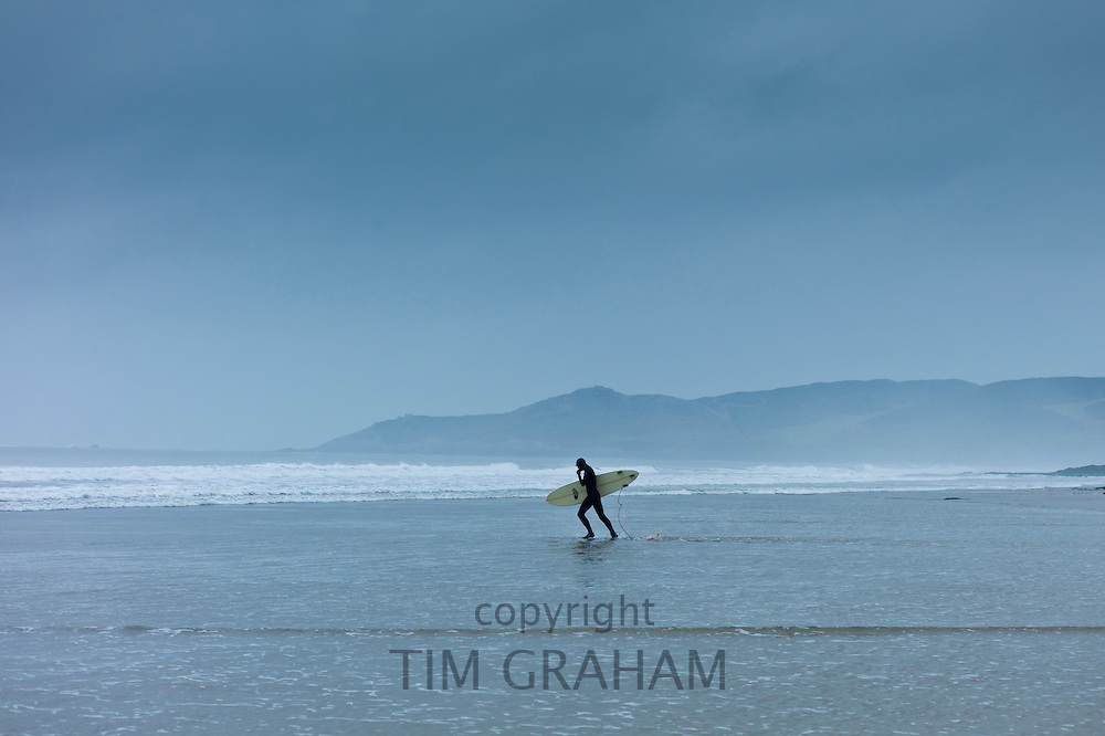 Surfer walking along the beach at Woolacombe, North Devon, UK