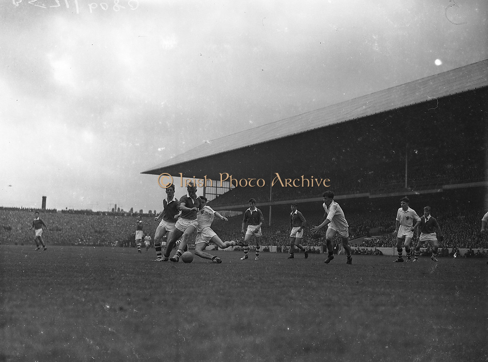 GAA All Ireland Minor Football Final Cork v. Galway 26th September 1960 Croke Park<br /><br />A.Ryan, Galway centre half back, tries to get a foot to the ball but Coughlan Cork Mid-Field player kicks the ball towards the goal *** Local Caption *** It is important to note that under the COPYRIGHT AND RELATED RIGHTS ACT 2000 the copyright of these photographs are the property of the photographer and they cannot be copied, scanned, reproduced or electronically stored in any form whatsoever without the written permission of the photographer  26th September 1960<br /> <br /> All Ireland Minor Football Final between Cork and Galway at Croke Park.