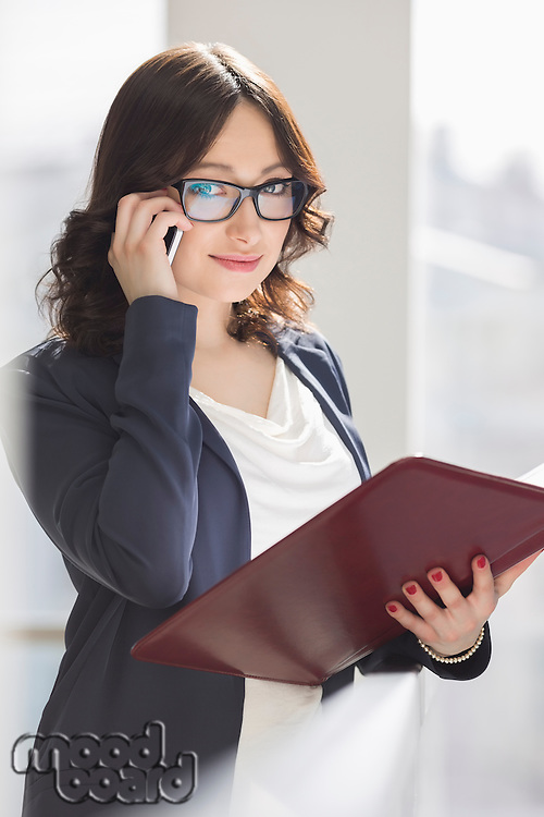Portrait of smiling businesswoman using cell phone while holding file in office
