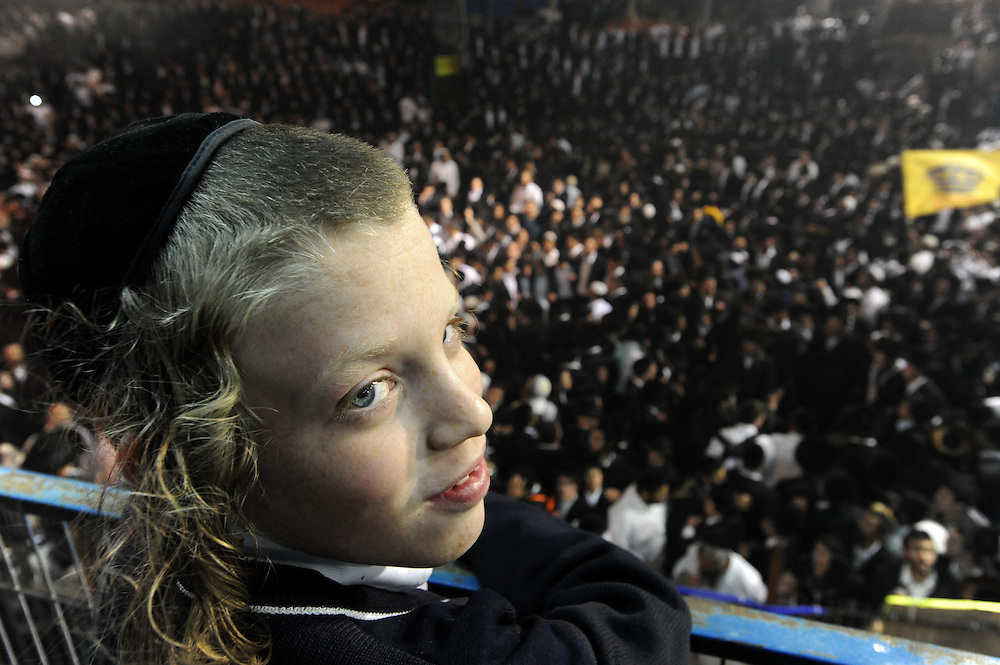 MERON, ISRAEL - MAY 02, 2010: An Ultra Orthodox Jewish kid watches  as dozens of thousands of Ultra Orthodox Jews dance and sing during the day-long holy Jewish holiday at the grave site of Rabbi Shimon Bar Yochai in the northern Israeli village of Meron, 02 May 2010. Lag Baomer commemorates Bar Yochai's death. Bar Yochai was a great scholar and one of the most important sages in Jewish history some 1800 years ago. Hundreds of thousands Jews light large bonfires all night long and visit his resting place in Meron