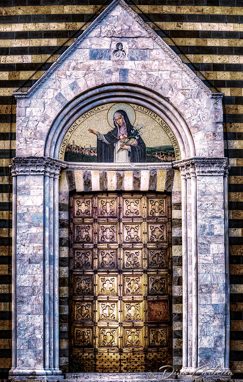 """""""Holy Door of the Church of Saint Agnes of Montepulciano""""... <br /> <br /> St. Agnes of Montepulciano was born in 13th-century Tuscany. At the age of six, Agnes began trying to convince her parents to allow her to join a convent. She was finally admitted to the Dominican convent at Montepulciano at age nine. Agnes' reputation for holiness attracted other sisters, and she became an abbess at the unheard of age of 15. She insisted on greater austerities in the abbey. She lived on bread and water for 15 years, slept on the ground and used a stone for a pillow. It was said that she had visions of the Virgin Mary and that in her visions angels gave her Communion. Agnes also had a vision in which she was holding the infant Jesus. When she awoke from her trance, she was holding the small gold crucifix the infant Jesus was wearing. She died in 1317. Miracles have been reported at her tomb. When her body was moved to a church years after her death, it was found incorrupt. She was canonized in 1726. The saint's shrine is located facing the 16th century ramparts of the Porta al Prato of Montepulciano. It opens into the lower part of the historical center and completed in 1306. The hill was chosen by the saint to build her church following visions of a stairway to heaven, it was originally occupied by brothels. Agnes purchased the land herself for 1,200 lire. The hill was transformed from a sinful location to a holy and reverent community. The church, monumental cloister, and its convent are now totally transformed and host the incorrupt body of Saint Agnes."""