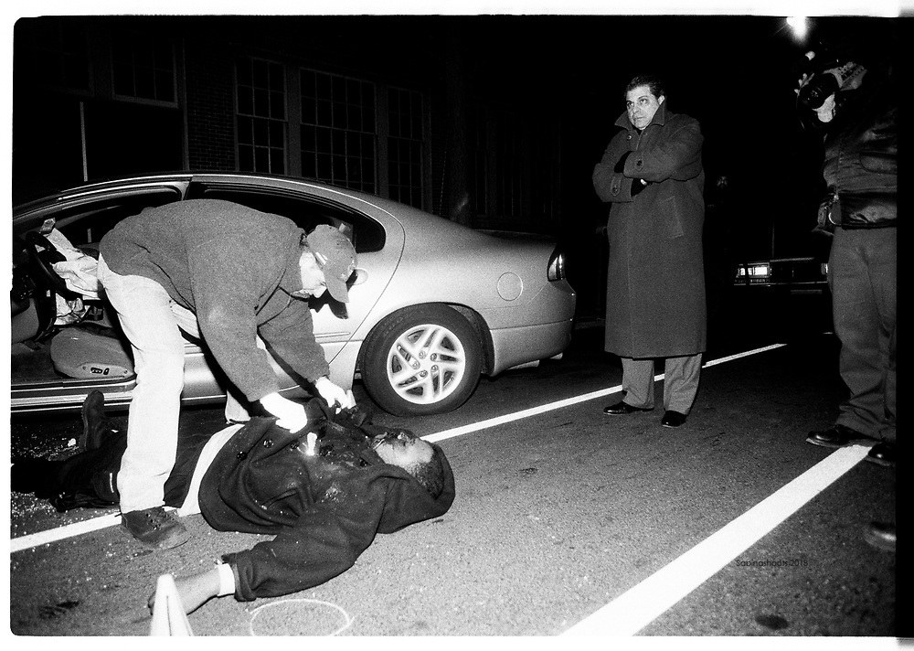 Homicide detectives examine a man that was shot in the back of his head by someone who was in the back of the car while he was driving. He was a drug dealer