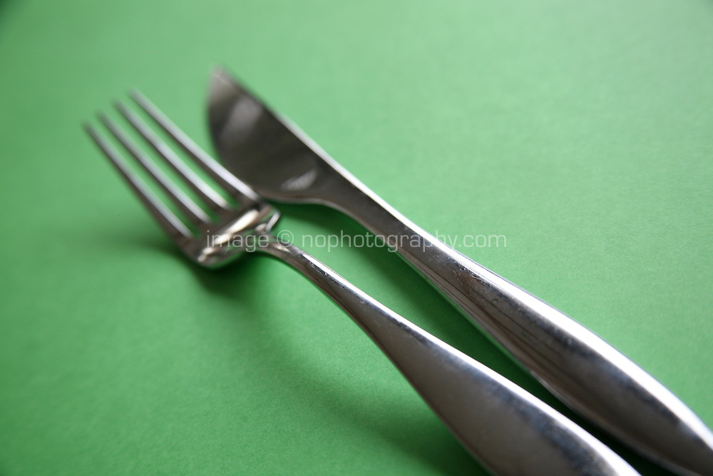 Knife and fork on colourful green background