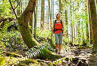 A woman hiking on a trail in a forest, Little Si Trail, Washington, USA.
