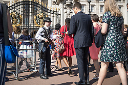 © Licensed to London News Pictures. 24/05/2017. London, UK. An armed police woman check passes for people entering Buckingham Palace for a garden party - security in the capital has been stepped up after the Manchester Arena bombing. The terrorism threat level has been raised to critical and Operation Temperer has been deployed. 5,000 troops are taking over patrol duties under police command. Photo credit: Peter Macdiarmid/LNP
