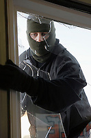 Masked thief braking in through window