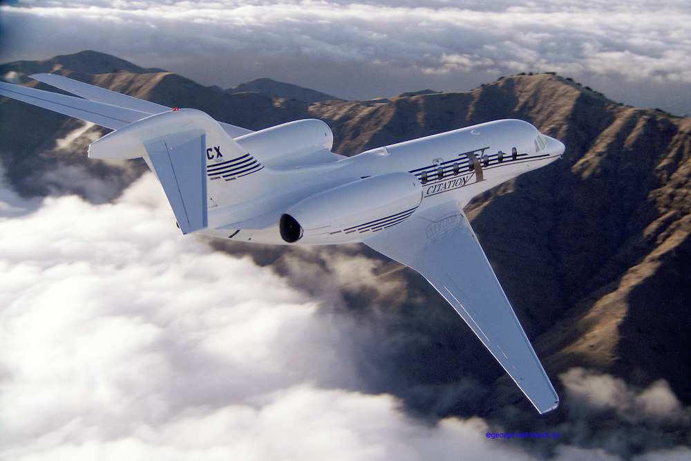 A Cessna Citation X flies over clouds and mountain tops.