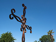 The ornate iron cross set against the deep blue sky at Lanne Soubiran church.