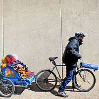 022813  Adron Gardner/Independent<br /> <br /> Flynn Donoho and his dog Diva leave the Gallup Independent after fixing a tire in Gallup Thursday.  Donoho is biking across America, though homeless, he is based out of California.