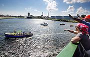 De Arctic Sunrise wordt welkom geheten als het Amsterdam binnenvaart. In IJmuiden is de Arctic Sunrise, het schip van milieuorganisatie Greenpeace dat een jaar door Rusland in beslag is genomen, aangekomen. De voormalige ijsbreker wordt in Amsterdam uit het water gehaald en opgeknapt omdat het gehavend is geraakt toen het aan de ankers lag. De boot van de milieuorganisatie is september 2013 door de Russen ge&euml;nterd en de bemanningsleden vastgezet op verdenking van piraterij. Greenpeace voerde actie bij een boorplatform in de Barentszzee. Als het schip weer is gerepareerd, wil de milieubeweging weer campagnes houden met de Artic Sunrise.<br /> <br /> In IJmuiden, the Arctic Sunrise, the Greenpeace ship that a year ago is seized by Russia, arrived. The former ice breaker is removed from the water in Amsterdam and refurbished since it was damaged when it was up to the anchors. The boat of the environmental organization is boarded in September 2013 by the Russians and the crew put down on suspicion of piracy. Greenpeace campaigned on a drilling platform in the Barents Sea. If the ship is repaired, the environmental movement wants to use the Arctic Sunrise again for campaigning.