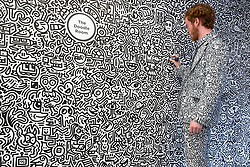 "© Licensed to London News Pictures. 07/04/2018. LONDON, UK. The artist Mr Doodle creates his distinctive artwork in The Doodle Room at ""Sense of Space"", an art pop-up which has opened to the public in Broadgate.  Comprising four rooms to challenge the visitor's sensory perceptions through art, the installation is open until 18 May.  Photo credit: Stephen Chung/LNP"