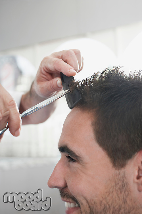 Barber cutting mans hair in barber shop