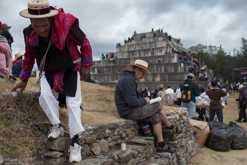 An indigenous man from San Juan Atitán descends a structure as a foreign tourist reads in the ancient Mayan site of Zaculeu during the celebrations marking the end of the Mayan Era known as 13 Baktun. Zaculeu, Huehuetenango, Guatemala. December 21, 2012.