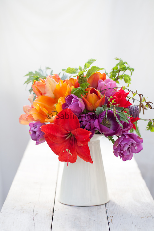 Flower arrangement with red Hippeastrum, orange and purple Tulips