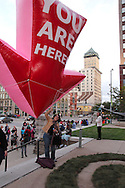 A visitor gets a picture taken under the 'you are here' balloon during the fall Urban Nights in downtown Dayton, Friday, September 14, 2012.