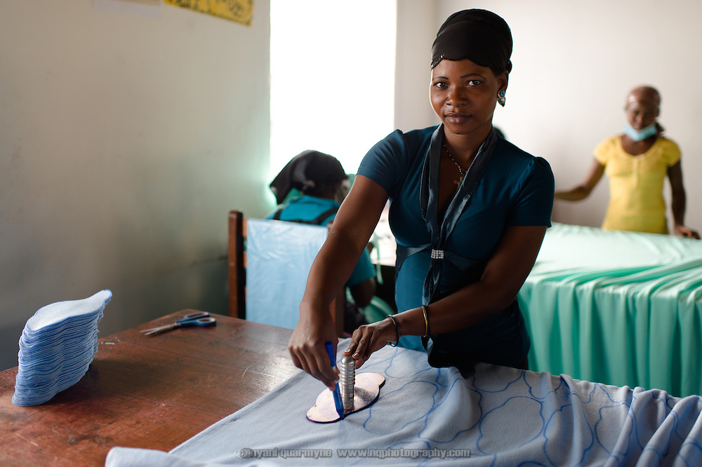Malia Nanyonga stencilling the outline of sanitary pads onto fabric before they are cut and sewn at the Afripads factory in the village of Kitengeesa in the Central Region of Uganda on 30 July 2014. Malia says she has been working at Afripads for a year, and that now that she has an income she is able to look after her children and her mother. She previously did odd jobs, such as working as a labourer. Started by volunteers in 2009, Afripads manufactures reusable fibre sanitary pads made locally by community residents. Beginning with a single employee, the company now employs roughly 100 women and produces approximately 700 kits (consisting of pads, holders and a bag) each week. At USh 12,000 to 15,0000 (£2.75 to £3.40) for a kit that lasts approximately one year, Afripads offer a significant saving over disposables which may cost in excess of USh 42,000 (£9.60) over the course of a year. And for the many girls and women who cannot afford disposables, they offer an affordable and more hygienic alternative to rags, cotton wool or toilet paper, all of which are frequently used. At schools where Afripads have been distributed, teachers report that absenteeism has dropped sharply as girls who previously did not have access to proper sanitary pads now no longer stay home when they have their periods.