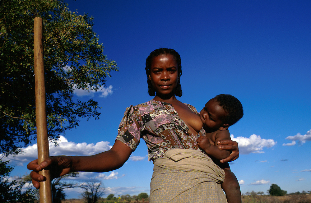 Woman collects water from well whilst breastfeeding her child, Betioky, Madagascar