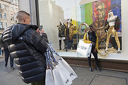 © Licensed to London News Pictures. 08/11/2018. London, UK.  Customer pose for photos outside the HM store in Oxford Circus with shopping bags of items from the Jeremy Scott H&M X Moschino collection. Photo credit: Ray Tang/LNP