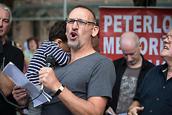 "© Licensed to London News Pictures . 16/08/2015 . Manchester , UK . CHRISTOPHER ECCLESTON amongst people reading an account of the "" Peterloo "" massacre at a memorial at the site of St Peter's Field , where fifteen people were killed during a cavalry charge on a democracy protest , 196 years ago (16th August 1819) . Photo credit : Joel Goodman/LNP"
