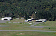 Wurtsboro, New York - An airplane, above hangar at right, takes off from Wurtsboro Airport in this view from atop the Shawangunk Ridge on Sept. 18, 2011. A row of gliders in parked on the grass in front of the hangars.