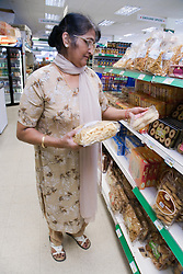Older woman in a supermarket shopping for groceries,