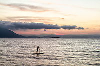 Silhueta de mulher remando stand up paddle na Praia do Ribeirão da Ilha ao por do sol. Florianópolis, Santa Catarina, Brasil. / Silhouette of a woman on a stand up paddle board at Ribeirao da Ilha Beach at sunset. Florianopolis, Santa Catarina, Brazil.