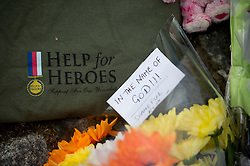 """© London News Pictures. 23/05/2013. Woolwhich, UK. Flowers and a """"help for Heroes"""" t-shirt left outside Woolwich Barracks in Woolwhich, London where a member of the armed forces was attacked yesterday (22/05/2013) by two men in what is being described as a terrorist attack. Photo credit: Ben Cawthra"""