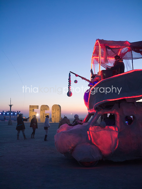 'Burners' dance to a roaming DJ truck while waiting for sunrise, Burning Man, Nevada