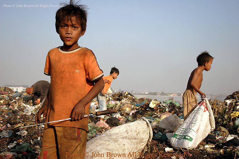 A young school-aged boy looks for recyclable material at The Stung Meanchey Landfill in Phnom Penh, Cambodia. He is one of 600 children who work at the dump on a daily basis. Most of the children are too poor to attend school.