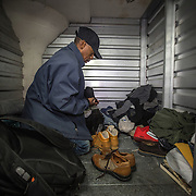 WASHINGTON, DC-OCT14: Leon Savoy, changes his shoes in his unit at Capital Self-Storage, October 16,  2015, before heading to his job as a furniture restorer. Savoy is currently homeless and living at a nearby shelter. Many of the area homeless have possessions they want to keep safe, just nowhere permanent to live, so they store their belongings at Capital Self-Storage, where an upper-level unit costs $30/month. Some of the homeless patrons also spend their days in their storage units, when shelters are closed during midday hours. The storage facility near 3rd and Florida Avenue in Northeast, Washington, DC, is about to be replaced by a boutique hotel. (Photo by Evelyn Hockstein/For The Washington Post)
