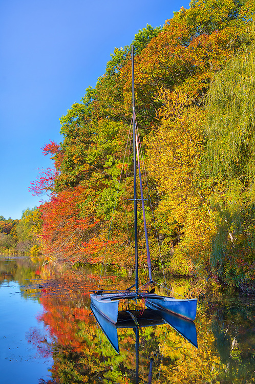 Massachusetts sailboat photography from Wellesley College at Lake Waban in Wellesley Massachusetts showing a catamaran framed by beautiful fall foliage. This Massachusetts lake with Wellesley College nearby are inspiring and make for a beautiful New England nature photography location to visit and to get lost with a camera.<br />