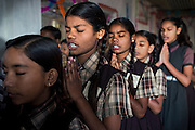 Poonam, 12, (centre) and her sister Jyoti, 13, behind her, are praying before lessons begin, while standing inside a classroom of the cozy, private school they regularly attend since 2011, located by their newly built home in Oriya Basti, one of the water-contaminated colonies in Bhopal, central India, near the abandoned Union Carbide (now DOW Chemical) industrial complex, site of the infamous '1984 Gas Disaster'. The two girls are studying in Year 6, out of 12, in 2015-16.