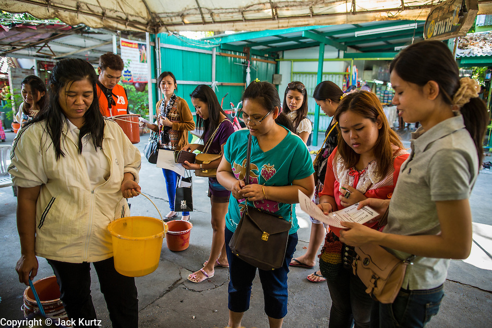 "03 JANUARY 2013 - BANGKOK, THAILAND: People buy live fish to release into Phra Khanong canal to ""make merit"" at Wat Mahabut. Just a few minutes from downtown Bangkok, the neighborhoods around Wat Mahabut interlaced with canals, still resemble the Bangkok of 60 years ago. Wat Mahabut is a large temple off Sukhumvit Soi 77. The temple is the site of many shrines to Thai ghosts. Many fortune tellers also work on the temple's grounds.   PHOTO BY JACK KURTZ"