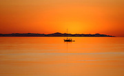 A sailboat is silhouetted as the setting sun casts a glow on a warm summer day on the Great Salt Lake in Utah.