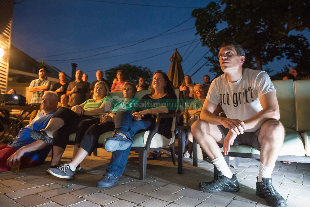June 11, 2017 - Merrick, New York, United States - 'American Grit' TV contestant CHRIS EDOM (wearing white  GOT GRIT? T-shirt), 48, of Merrick, hosts backyard Viewing Party for Season 2 premiere. Edom family relatives and neighbors watched Episode 1 of FOX network reality television series that Sunday night outdoors. Edom was last of 16 contestants picked for a team that episode. (Credit Image: © Ann Parry via ZUMA Wire)