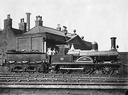 North Staffordshire Railway steam Locomotive No 14 and its tender.  This 2-4-0 locomotive, pictured with driver and fireman on the footplate, was built by Dubs & Co. of Glasgow and delivered in 1875. Photograph.