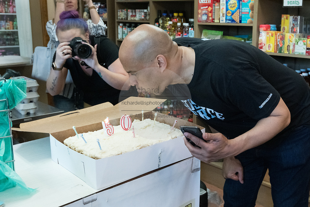 Democratic presidential hopeful Senator Cory Booker blows out the candles on his birthday cake during a visit to Fresh Future Farm April 27, 2019 in North Charleston, South Carolina. Booker spent his 50th birthday helping out at the urban farm as part of his Justice For All tour.